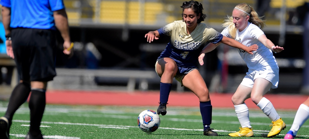 Gallaudet's Sharon Castillo dribbles the soccer ball past a defender on a sunny afternoon on a soccer field.