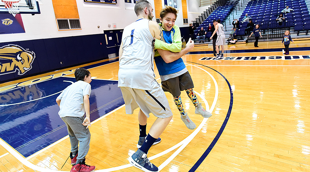 Steve Valencia-Biskupiak plays with two of his four kids on the floor for Gallaudet before his team's game. (Gallaudet athletics photo)