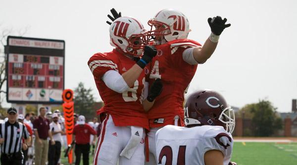 Jonathan Stoner (81) and Stephen Zumdick (84) celebrate a second-quarter touchdown for the Tigers as they romped past Chicago, 41-17. Photo by Erin Pence