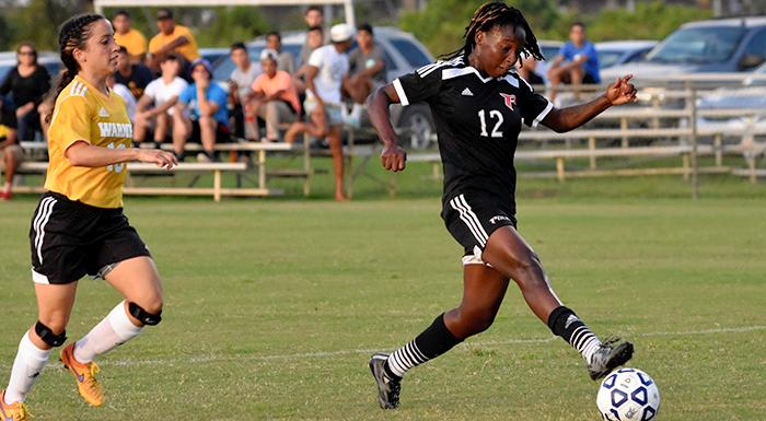 Shinell McCalla beats a Warner defender to score Polk State's first goal in a 3-2 win. (Photo by Tom Hagerty, Polk State.)