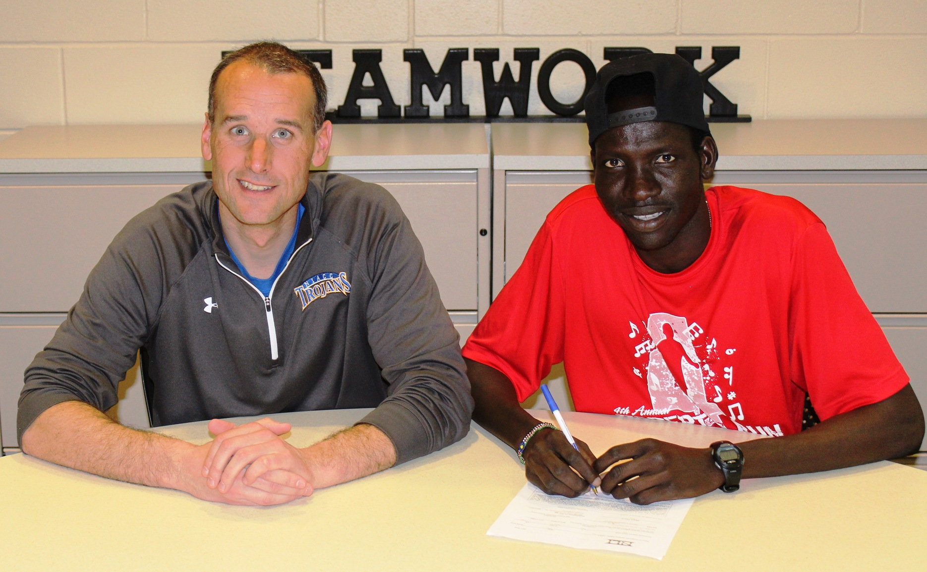 NIACC's Wal Khat, with his coach Curtis Vais, signed a national letter of intent Thursday to run at the University of Northern Iowa.