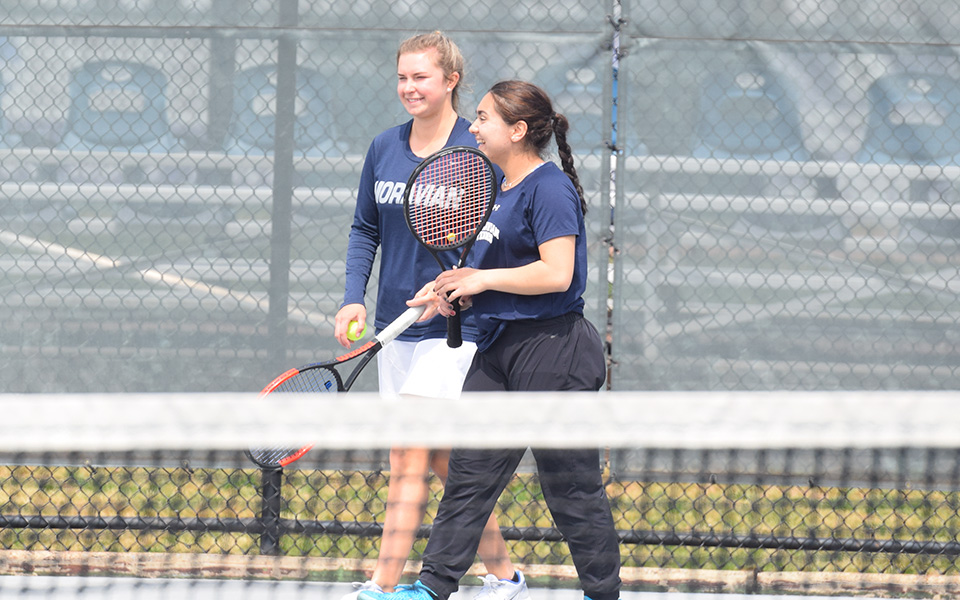 Junior Eiman Nazif and sophomore Emma Angle celebrate winning a point in doubles action versus Goucher College at Hoffman Courts.