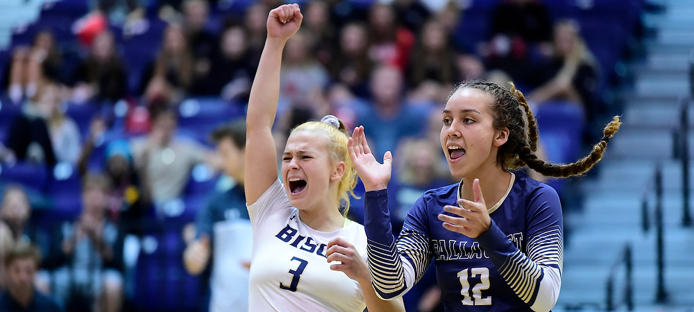Malia Zornoza (right) and Leila Sicoli (left) celebrate a point in a women's volleyball match.