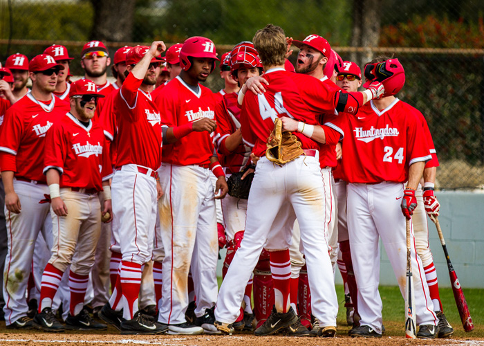 Huntingdon players celebrate after the first of five home runs in Saturday's doubleheader against Greensboro. The Hawks won the first game 16-4 and took the second game 16-7. (Photo by Christopher Morgan).