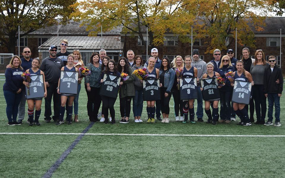 Seniors Sara Cruz, Devyn Lapp, Ashley Magee, Kylie Mastricola, Olivia Schlofer, Elisa Silecchia and Hayley Wrazien with their families on Senior Day versus The Catholic University of America on John Makuvek Field.