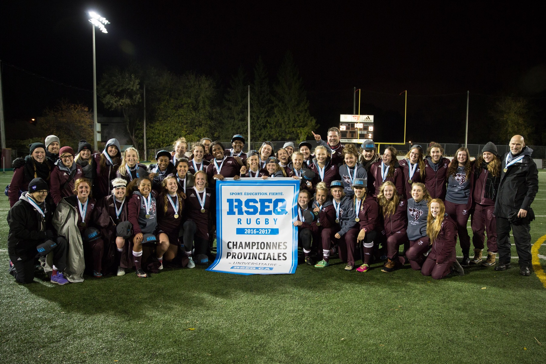 Team holds 2016 RSEQ championship banner at Matt Anthony Field.