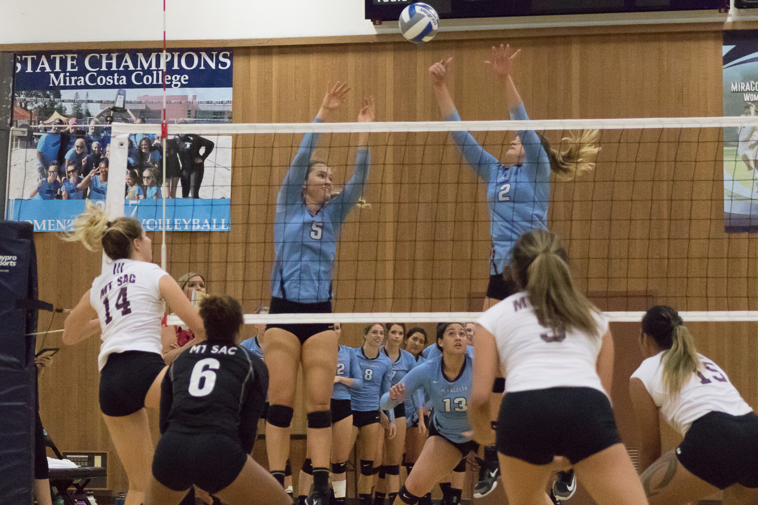 Spartan volleyball players block a ball.