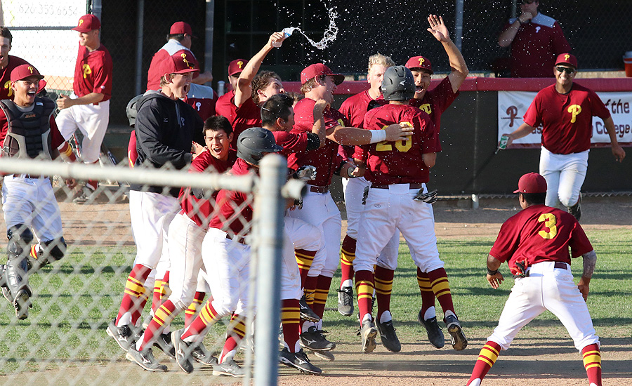 The first-place PCC baseball team celebrates a walk-off win as they swarm John Bicos, who scored the final run on a wild pitch Tuesday, photo by Richard Quinton.