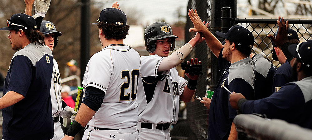 Members of the baseball team give high fives to each other in the dugout.