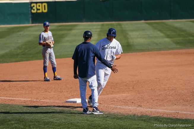 Cody Ahrens is greeted by third base coach Ron Perodin after his home run