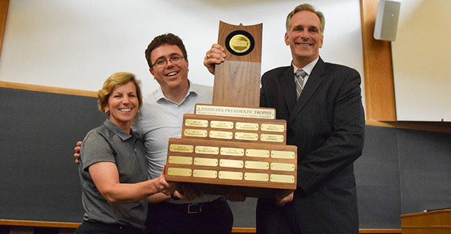 Mary Beth Spirk, Landmark Conference Commissioner Dan Fisher and President Bryon L. Grigsby '90 with the Landmark Conference Presidents' Trophy at the final faculty meeting of the 2017-18 academic year.