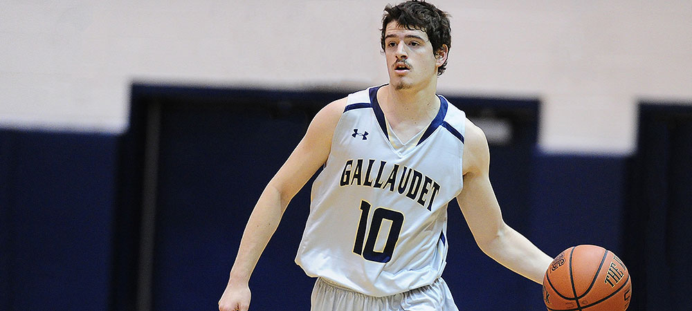 Gallaudet men's basketball guard Noah Valencia dribbles the ball up the court in a game. The basketball is in his left hand while his right arm is down beside his body. He is wearing a gray Gallaudet jersey with the number 10 on it in blue.