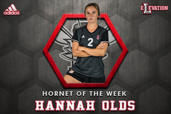 Hannah Olds standing in uniform on honeycomb gray hornet of the week background.