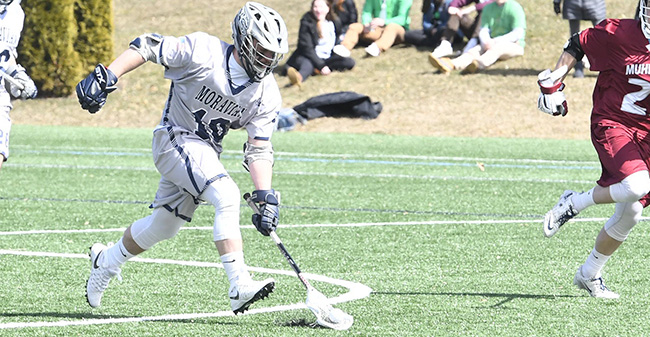 Rick Guerra '19 scoops up a ground ball after winning a face-off versus Muhlenberg College.