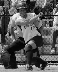 Black and white action photo of Meghan Sargent playing softball