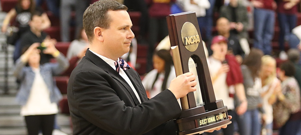 Gallaudet's Sam Atkinson holds a NCAA Division III men's basketball sectional championship trophy as he presents it to Springfield College.