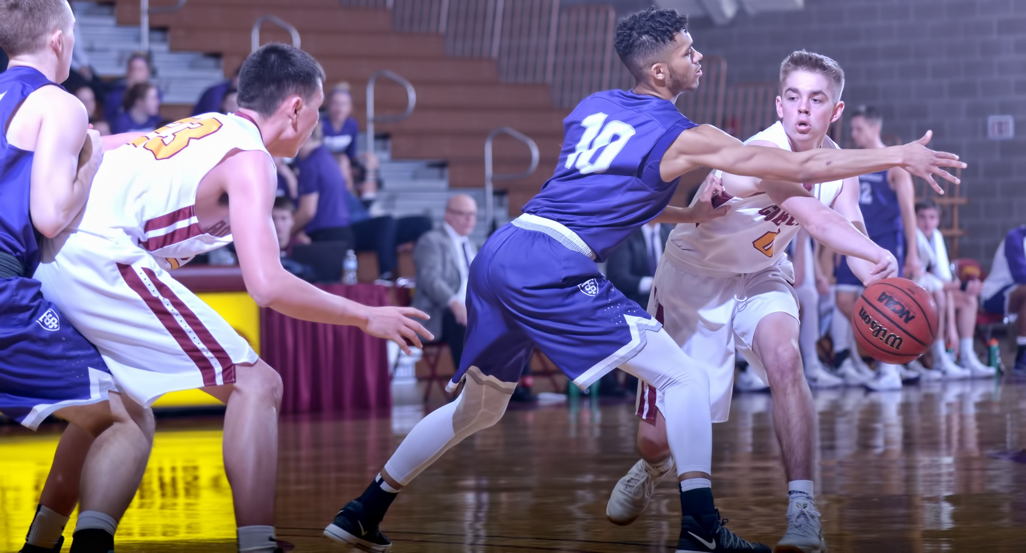 Sophomore Hunter Larson reaches around to make an entry pass to teammate Jordan Davis during the second half of the Cobbers' game vs. St. Thomas. (Photo courtesy of Greta Nye)