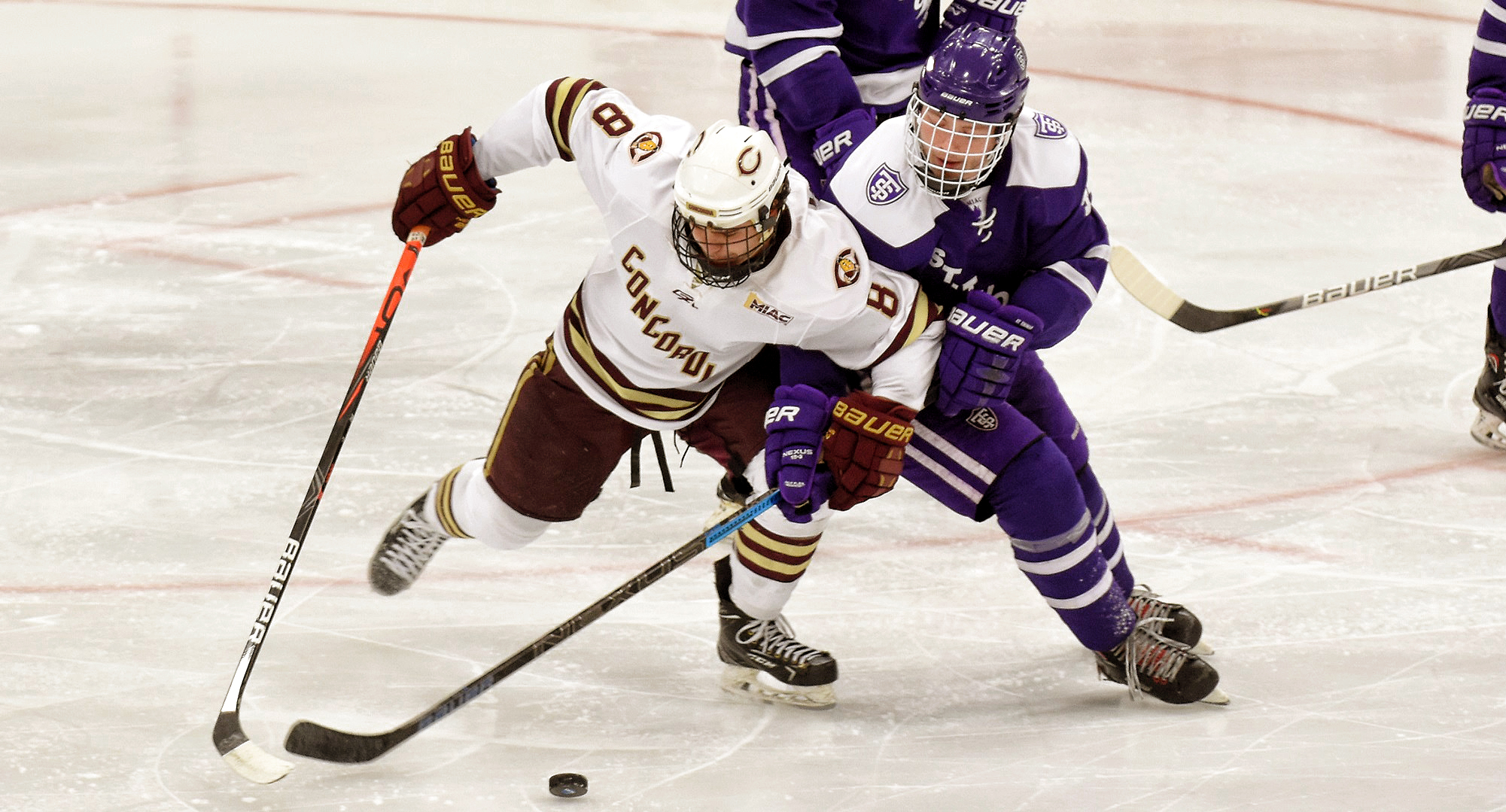Aaron Herdt gets tied up with a St. Thomas defensive player in the second period of the Cobbers' series finale with UST. Herdt had one of Concordia's two goals on the day.