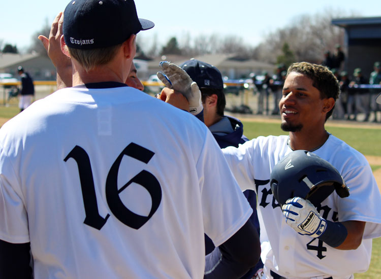 Trojans shortstop Enok Perez is congratulated by Adam Cook (16) after hitting a two-run home run against Seward County in the first of two games March 17 at Young Memorial Field. Perez also homered in the second game. Colby won both contests, 7-0 and 11-1.