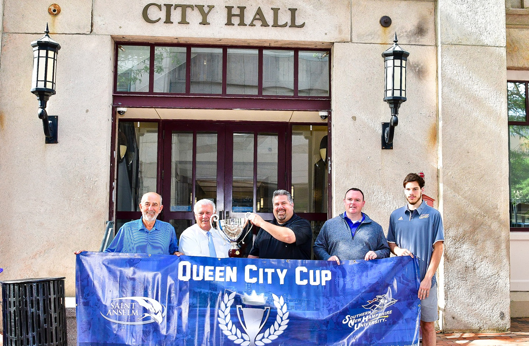 Members of the SNHU athletic department accept the 2016-17 Queen City Cup from Manchester Mayor Ted Gatsas.