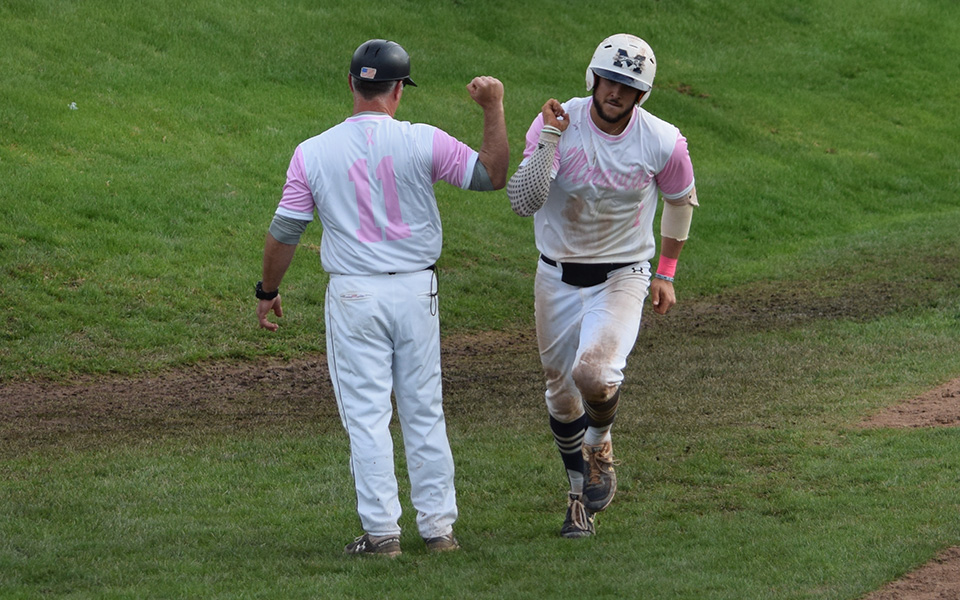 Senior Austin Markowski gets a high five from Head Coach Paul Engelhardt after rounding third base on his home run in the second game of a doubleheader versus The United States Merchant Marine Academy as the Greyhounds wore special pink jerseys for Breast Cancer Awareness Day at Gillespie Field.