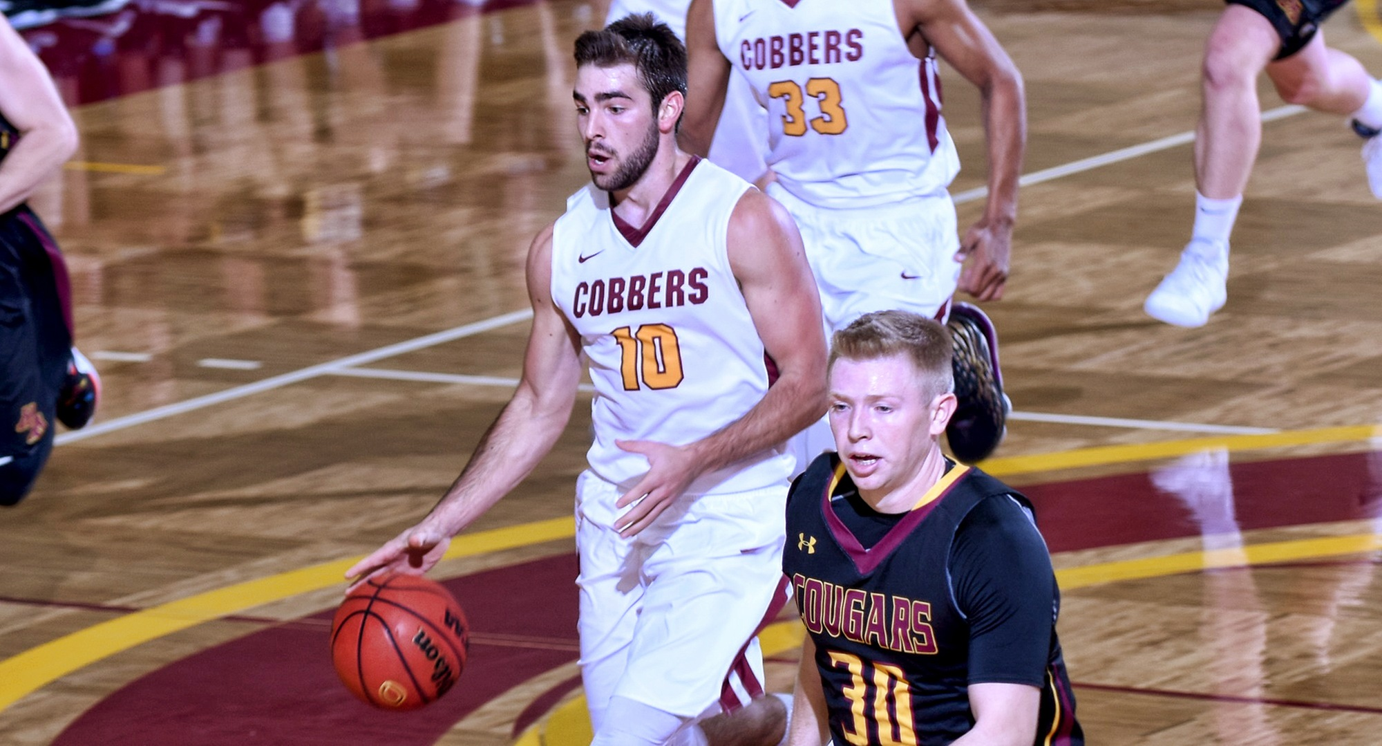 Senior Tommy Schyma dribbles the ball up the court on the fast break during the Cobbers' season opener with Minn.-Morris. He led all players with 27 points.