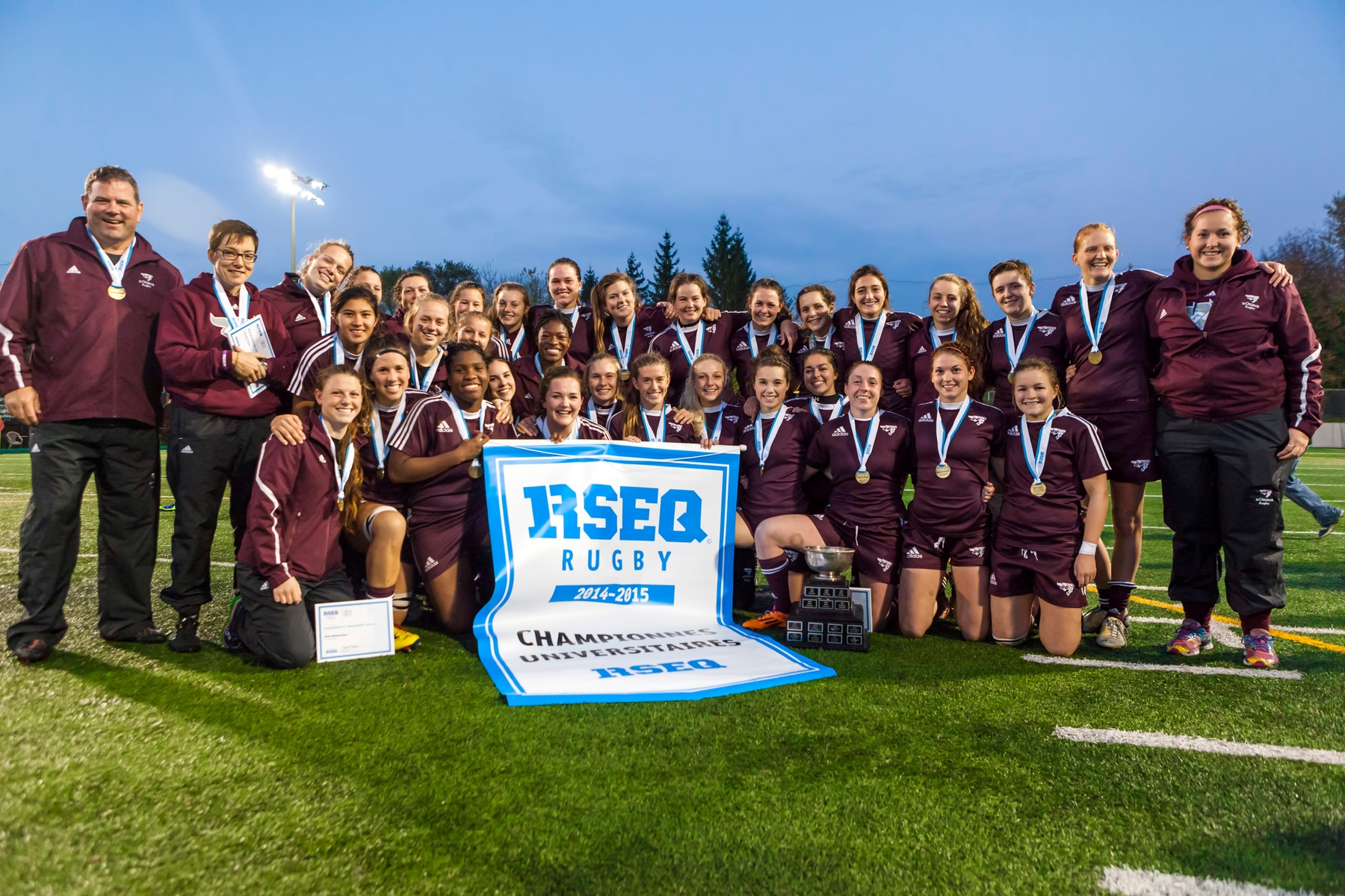 Team holds 2014 RSEQ championship banner at Matt Anthony Field.