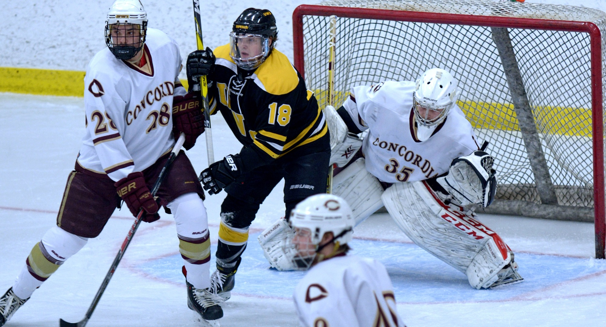 Sophomore defenseman Turk Scatliff ties up  a Wis.-Superior attacker as goalie Sam Nelson tries to see the puck in the Cobbers' 3-2 win.