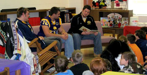 Football players read to students at Cane Creek Elementary