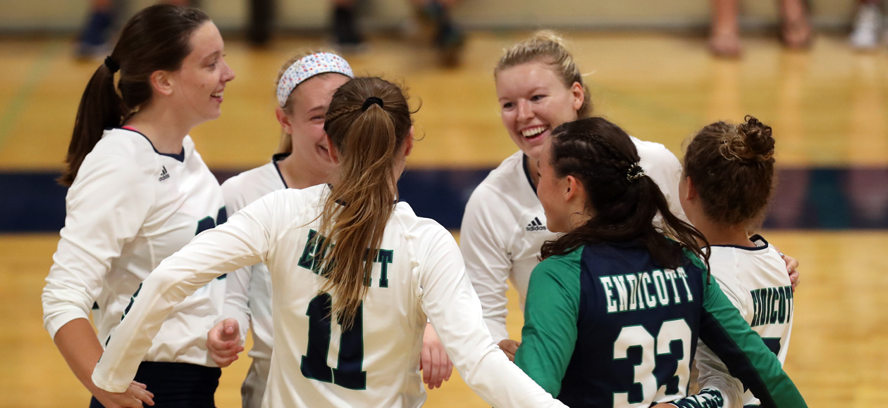 Image of the Endicott women's volleyball team huddled on the court.