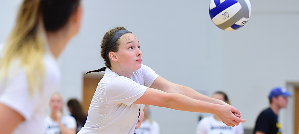 GU's Farrah Harmount makes a dig in a volleyball match. The volleyball flies upwards off her arms.