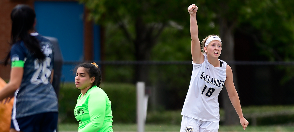 Payton DeGraw celebrates after she scores a women's soccer goal for the Gallaudet Bison. She raises her right arm in the air in celebration. Go Bison!