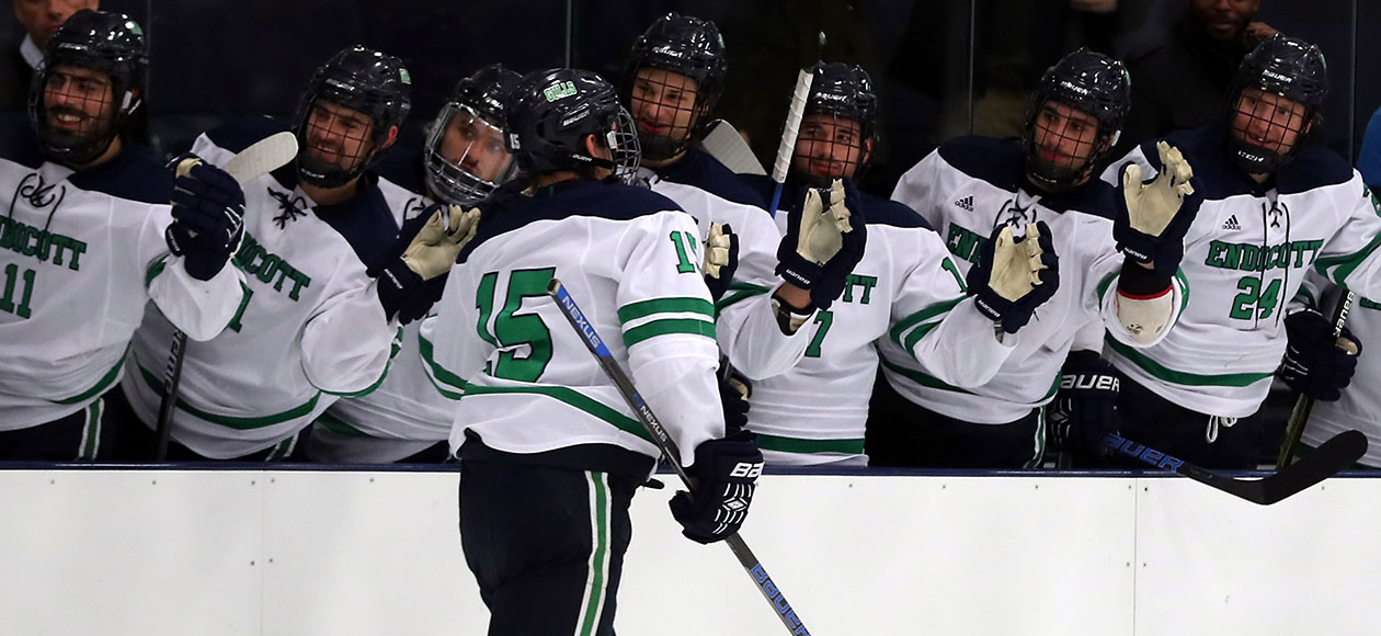 Josh Bowes skates by the Endicott men's ice hockey bench and high-fives his teammates.