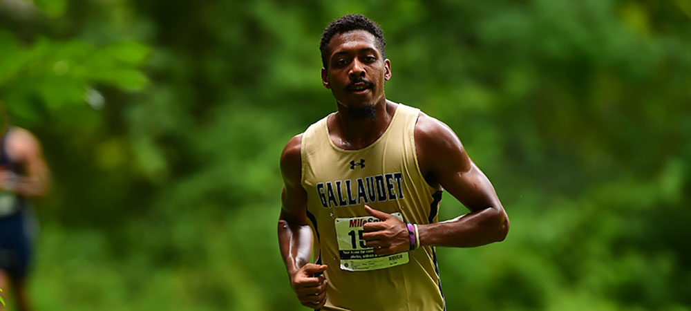 Gallaudet men's cross country runner in the field wearing a gold Gallaudet jersey with GALLAUDET in dark blue letters across the front and his number pinned below.