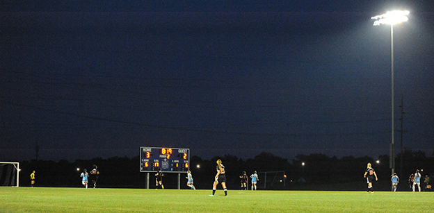 Several soccer players are visible at the bottom of the image during a night game at the Purcell Athletic Fields soccer field. A tall light is visible at the right of the image.