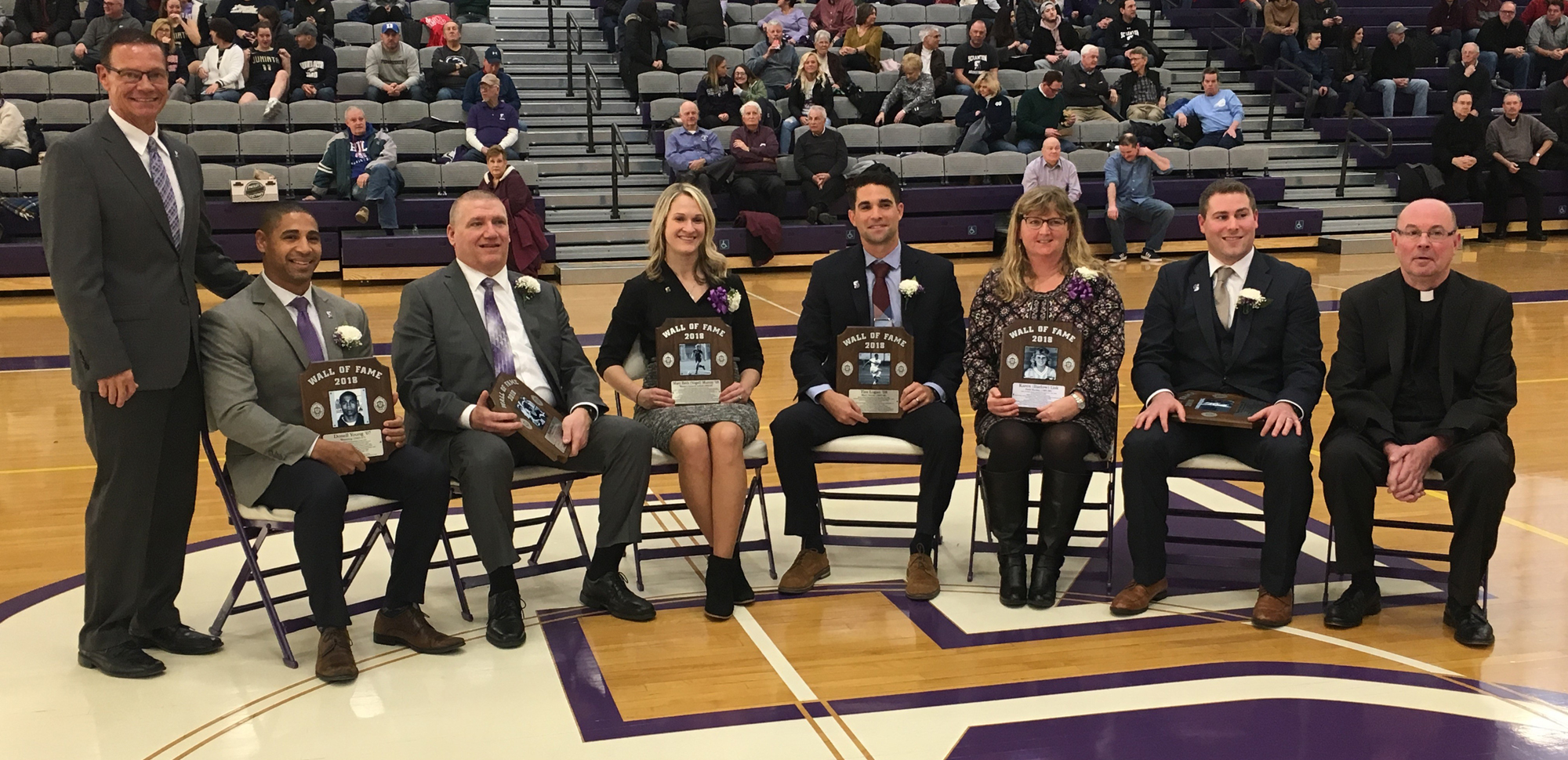The Wall of Fame Class of 2018, seated from left: Donell Young'07, Frank Ross '87, Mary Beth (Vogel) Murray '08, Tim Logan '08, Karen (Barlow) Lisk '89, and Randy Arnold '08. Seated at the far right is Fr. Scott Pilarz, S.J., president of the University while Dave Martin, director of athletics, is standing at the far left.