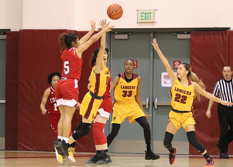 Lancer Daniela Mendez gets her hand on Palomar's Julie Saelee's 3-point attempt for the block that helped PCC win its Round 2 Regional Playoff Friday night, photo by Richard Quinton.