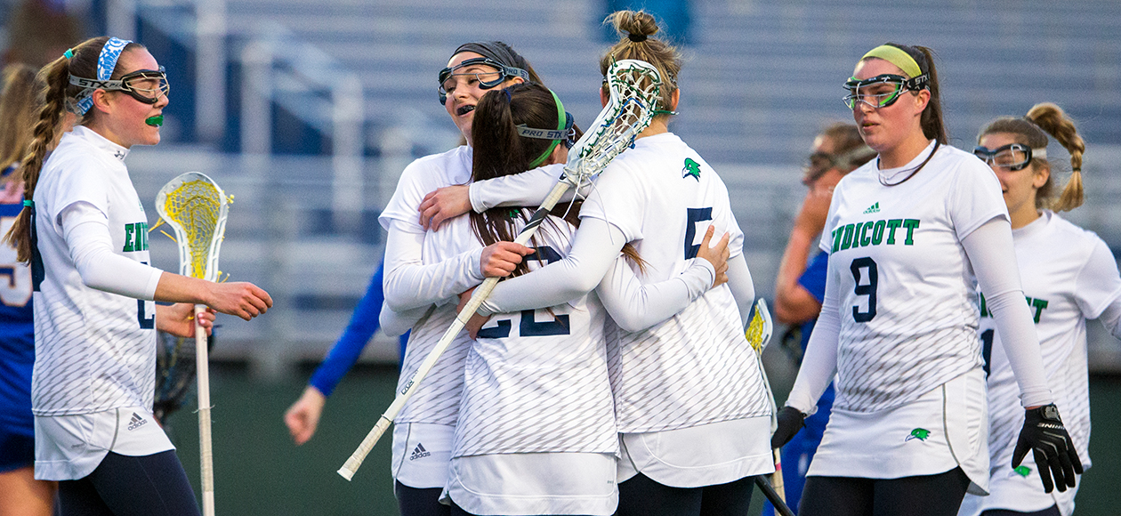 Members of the Endicott women's lacrosse team celebrate a goal.