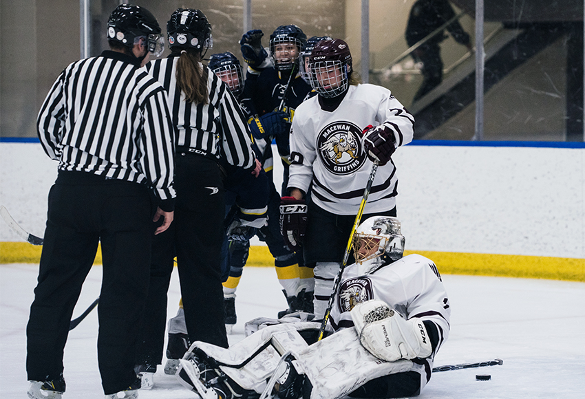 NAIT players celebrate one of four goals on MacEwan's Sandy Heim on Saturday night (Matthew Jacula photo).