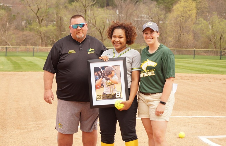 Graduating player Yesileidy Paulino receiving her framed photo with coaches Meagan Hillard and Greg Keesler on grad day.