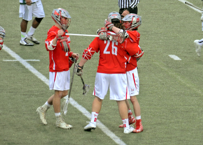 Brandon Scheele (#26) is congratulated after scoring the winning goal in Thursday's 12-11 overtime win against Greensboro. Scheele finished with three goals and an assist. (Photo by Sydney Robbins)