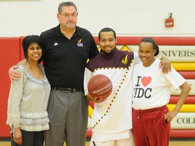 Senior guard Brandon Herbert was honored before the game for reaching the 1,000-point career milestone last Saturday. Pictured from L to R: Athletic Director Patricia Thomas, Head Coach Jeff Ruland, Brandon Herbert, and Brandon's mother.
