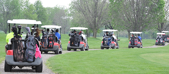 A line of golf carts drives out along a gravel path to begin the golf outing.
