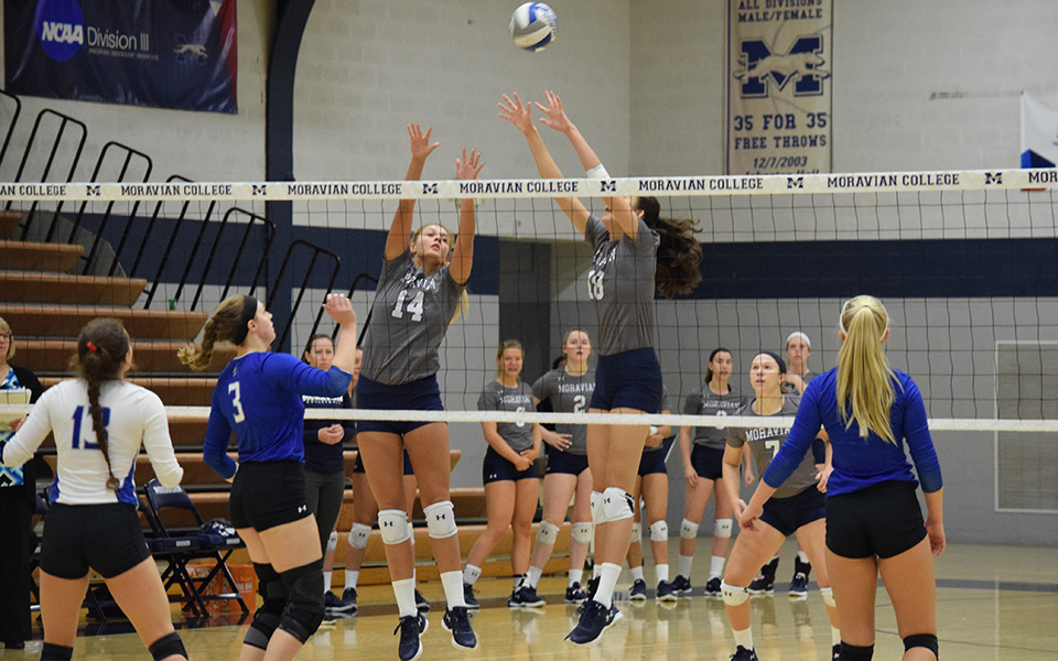 Sela Herber and Renee Mapa on a block attempt versus Elizabethtown College in Johnston Hall during the 2018 season.
