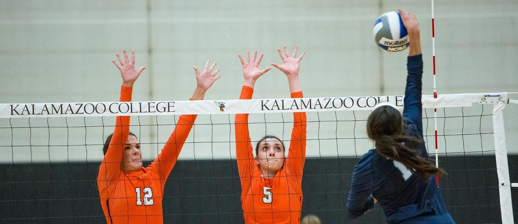 Kalamazoo College volleyball players jumping at the net.