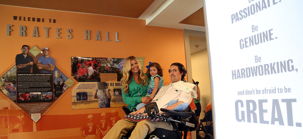 Pete Frates, his wife, and his daughter stop for a photo in front of the Welcome To Frates Hall sign in Pete Frates Hall.
