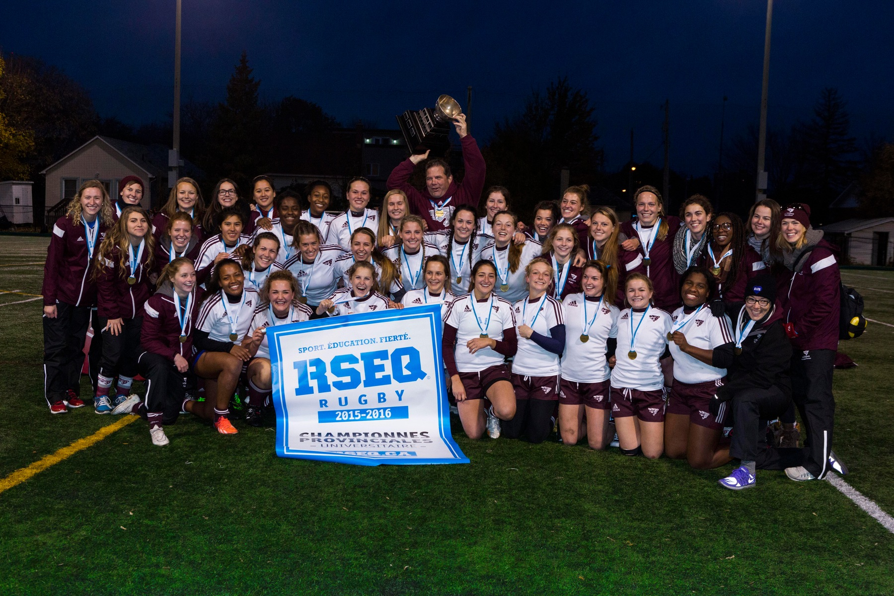 Team holds 2015 RSEQ championship banner at Matt Anthony Field.
