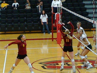 Samantha Fordyce (#11) sets the ball up for an attack by Sarah Lark (#9) in action versus Wayne State (Neb.).