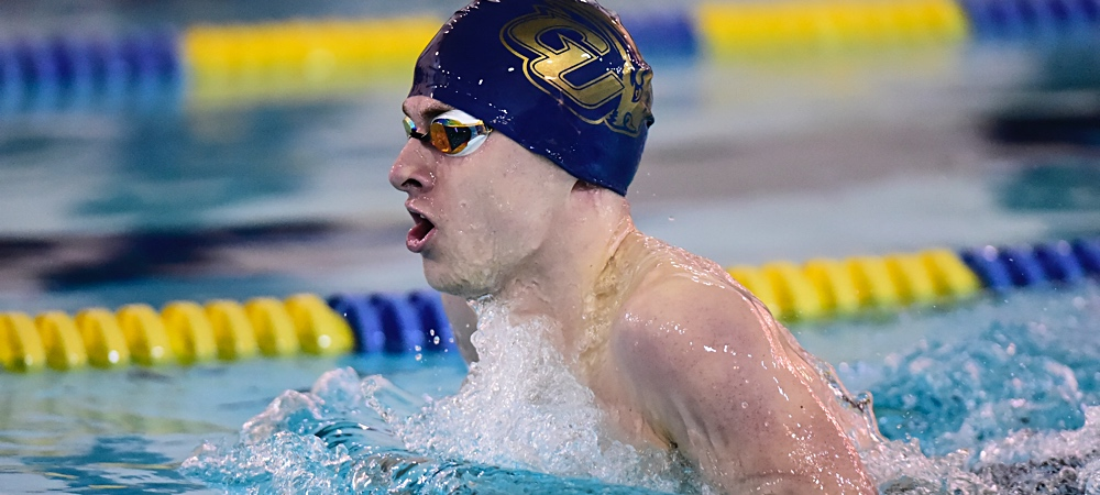 GU sophomore Ben Sealts performs the breaststroke in a swim meet in a pool. He is wearing a navy blue Gallaudet Bison swim cap.