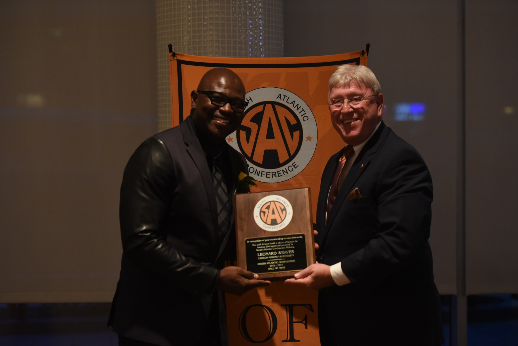 Leonard Weaver accepts his SAC Hall of Fame plaque from C-N Director of Athletics Allen Morgan